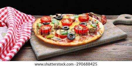 Tasty pizza with vegetables and basil on black background