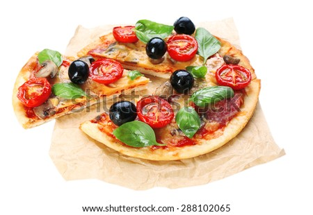 Tasty pizza with vegetables and basil on paper isolated on white - stock photo