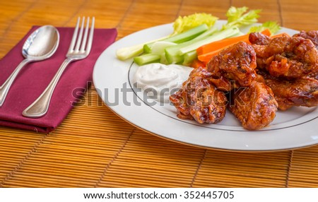 Tasty plate of glazed chicken wings with carrots, celery and dipping sauce.  - stock photo