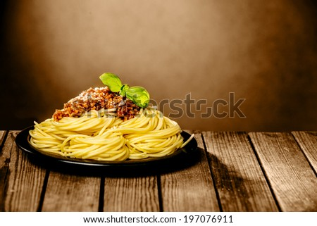 Tasty plate of spaghetti Bolognaise sprinkled with parmesan cheese and garnished with fresh basil served in a rustic restaurant with copyspace on a brown wall - stock photo