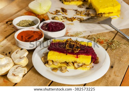 Tasty polenta with mushrooms and tomatoes. - stock photo