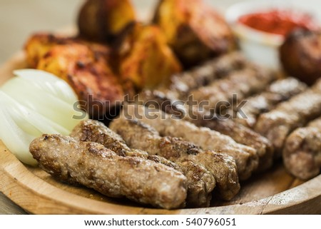 Tasty pork kebabs, cevapi or cevapcici as they are known in traditional Balkan cuisine, served with seasoned baked potatoes and onions
