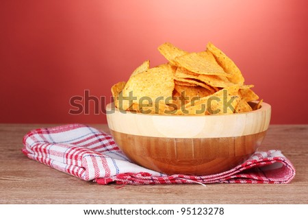 tasty potato chips in wooden  bowl on wooden table on red background - stock photo