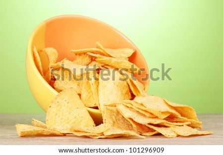 tasty potato chips in yellow  bowl on wooden table on green background - stock photo