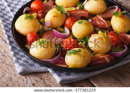 Tasty potatoes with onion, tomato and bacon on a plate. horizontal  - stock photo