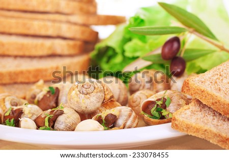 Tasty prepared escargot with bread and olives on the plate, luxury dinner in expensive restaurant, traditional French delicatessen, delicious food concept - stock photo