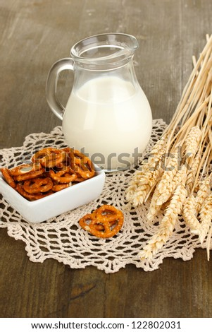 Tasty pretzels in white bowl and milk jug on wooden table close-up