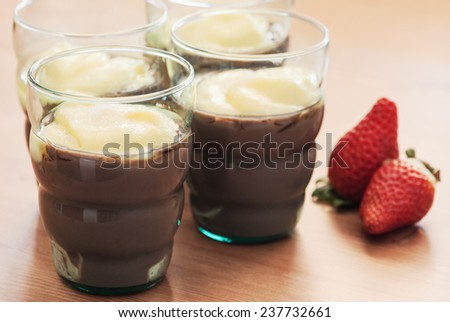 Tasty pudding and fresh strawberries on the table. - stock photo