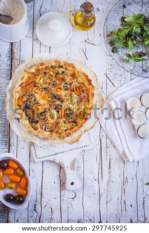 Tasty puff pastry quiche with mozzarella cheese, mushroom and colorful tomato served on decorative rustic cutting board from above on a shabby chic white wood table with green leaves for salad. - stock photo