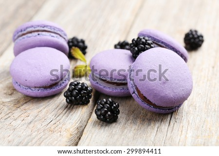 Tasty purple macarons with blackberry on grey wooden background - stock photo