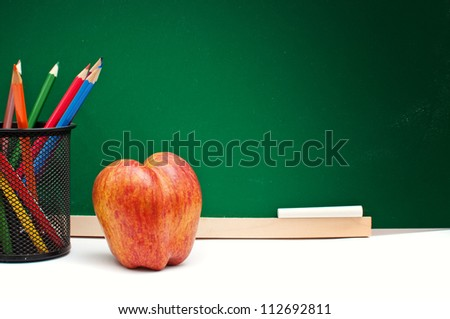 Tasty red apple and color pencils in front of the green chalkboard, back to school concept - stock photo