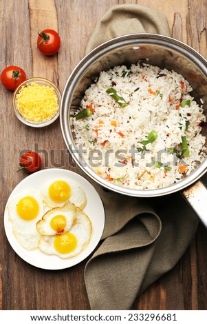 Tasty rice in pan on wooden table - stock photo