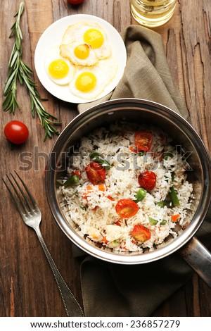 Tasty rice in pan on wooden table - stock photo