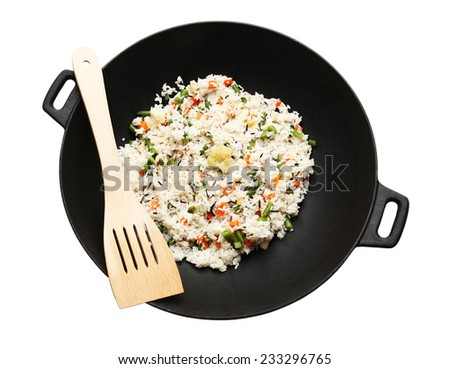 Tasty rice preparing in wok, isolated on white - stock photo