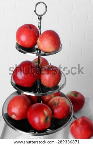 Tasty ripe apples on serving tray on brick wall background - stock photo