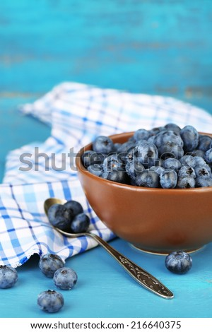 Tasty ripe blueberries in bowl, on wooden table - stock photo