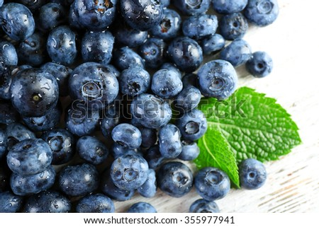 Tasty ripe blueberries with green leaves close up - stock photo