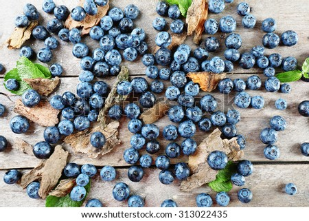 Tasty ripe blueberries with green leaves on wooden table close up - stock photo