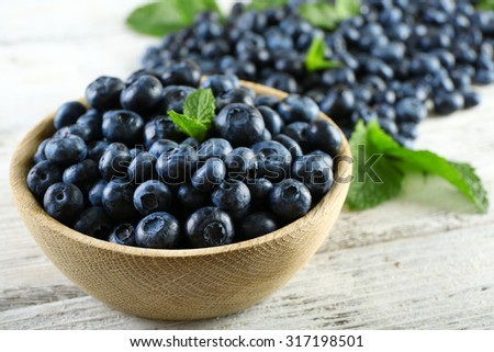 Tasty ripe blueberries with mint in bowl on table close up - stock photo