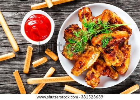 tasty roasted chicken wings on a white dish, tomato sauce in a gravy boat and bread sticks on an old wooden table,  top view - stock photo
