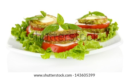 Tasty roasted marrow and tomato slices with salad leaves, isolated on white