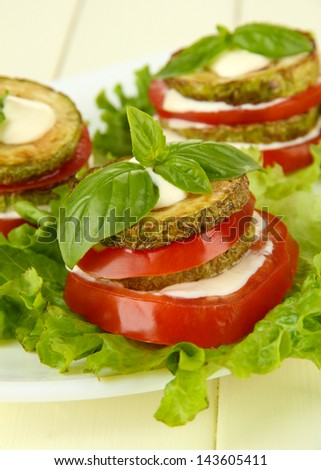 Tasty roasted marrow and tomato slices with salad leaves, on wooden background