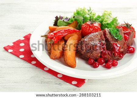 Tasty roasted meat with cranberry sauce and roasted vegetables on plate, on color wooden background - stock photo
