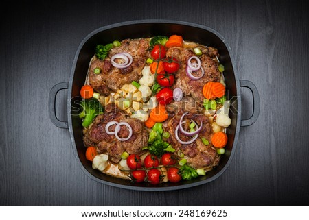 Tasty roasted pork meat with mushrooms and vegetable  - stock photo