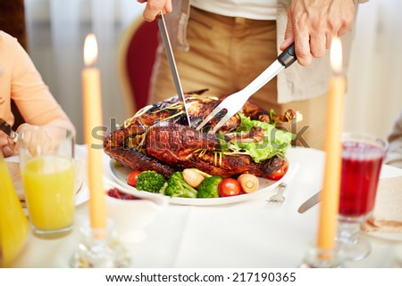 Tasty roasted poultry on festive table being cut by a man - stock photo