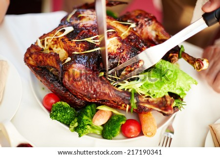 Tasty roasted turkey with vegetables being cut by a human - stock photo