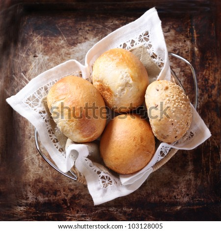 Tasty rolls lying on a white napkin in a basket - stock photo