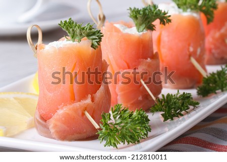 Tasty rolls of red fish with cottage cheese closeup on the table. horizontal  - stock photo