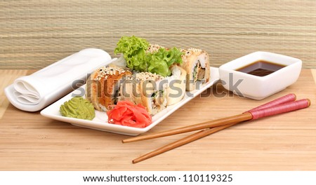 Tasty rolls served on white plate with chopsticks on wooden table on light background - stock photo