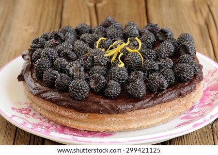 Tasty round homemade chocolate pie with ganache, decorated with fresh blackberries, lemon peel and icing sugar in white plate on wooden table - stock photo