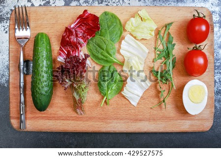 Tasty salad on the wooden board in the restaurant. Lettuce, cucumber, cabbage, tomato, egg on the chopping board next to the silver fork on the black table. Restaurant food - stock photo