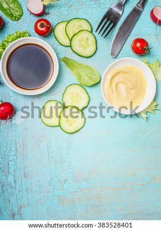 Tasty salad preparation with vinegar and mustard dressings and cutlery on light shabby chic blue background, top view, place for text. Healthy eating or diet food concept. - stock photo