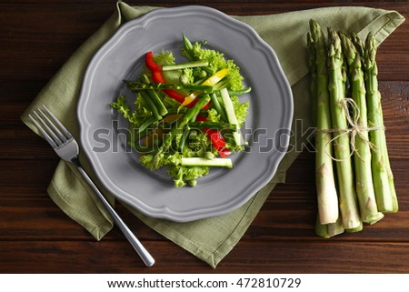 Tasty salad with asparagus and vegetables on plate