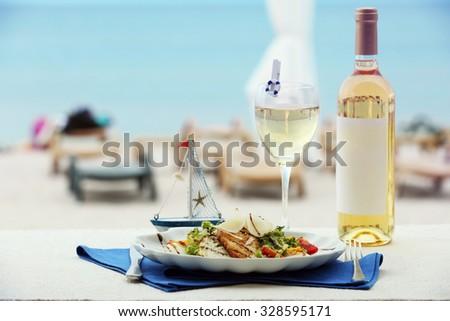 Tasty salad with served wine on blue napkin - stock photo