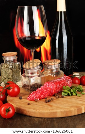 Tasty salami on board wooden table on fire background