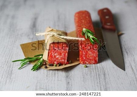Tasty salami sausage, on paper on wooden background - stock photo