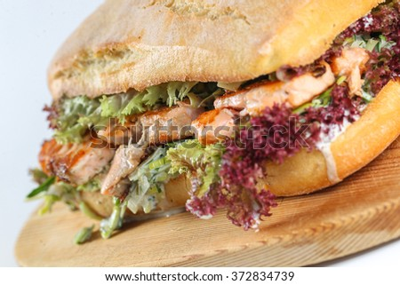 Tasty salmon steak sandwich in a ciabatta with lettuce, scallion sauce, capers, dill and basil - stock photo