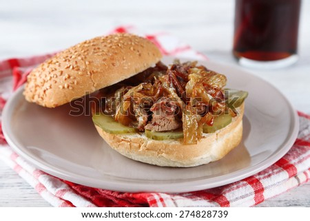 Tasty sandwich on plate and glass of cold drink, on wooden table background, close-up Unhealthy food concept