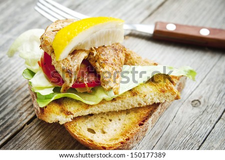 tasty sandwich with grilled chicken, salad,tomato,toast and a slice of lemon
