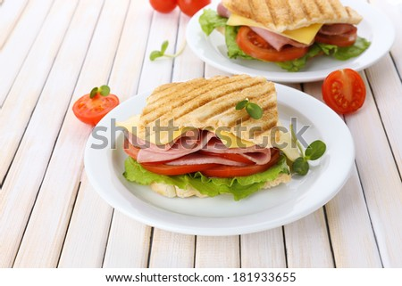 Tasty sandwich with ham on wooden table - stock photo