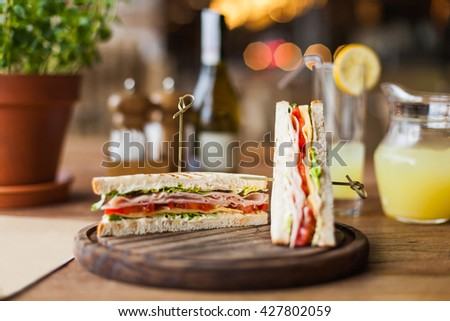 tasty sandwich with ham, tomato, lettuce, cheese on the wooden plate in the restaurant - stock photo