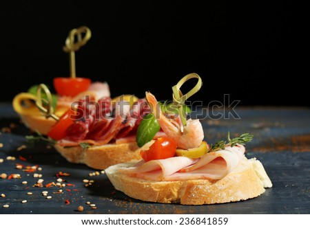 Tasty sandwiches on wooden table, on black background - stock photo