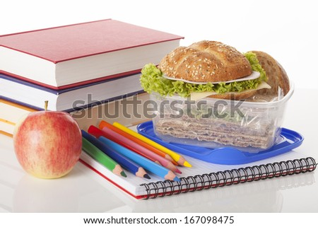 Tasty sandwiches with green lettuce in container and school supplies - stock photo