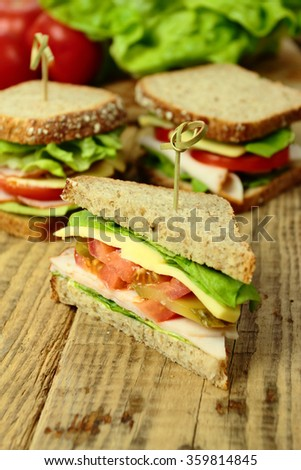 Tasty sandwiches with ham, cheese and fresh vegetables - stock photo