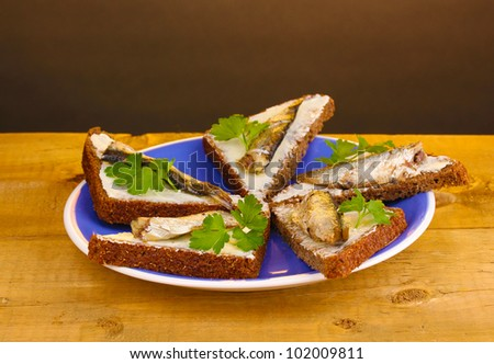 Tasty sandwiches with sprats on plate on wooden table on brown ...