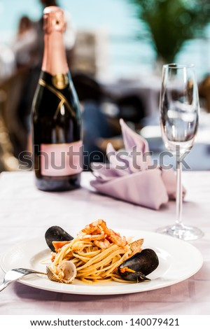 tasty seafood linguine pasta served with a bottle of bubbly champagne